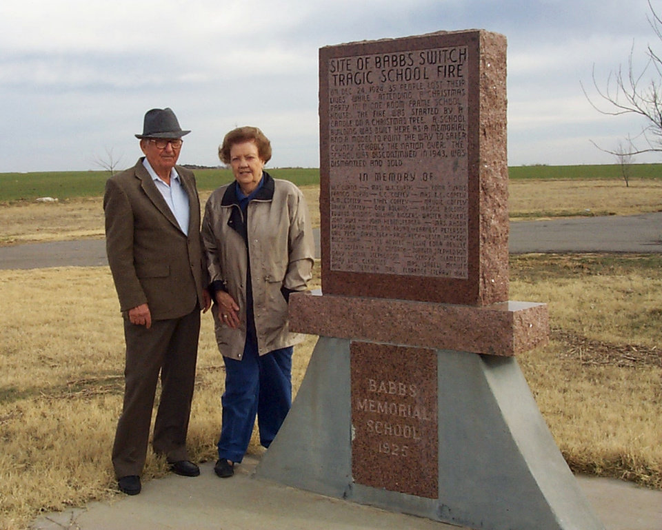 Photo - Babbs Switch schoolhouse fire survivors Joe Hebensperger and Lillie Biggers Braun stand by a monument to those who died in the Christmas Eve fire.