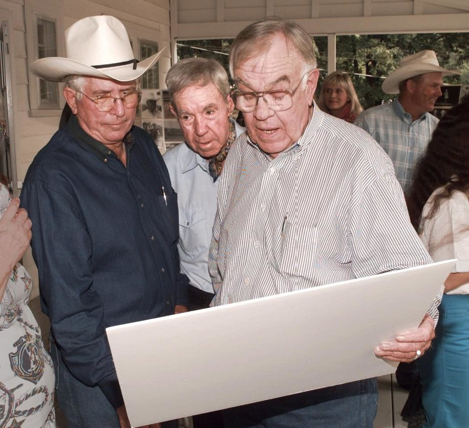 Photo - Former world champion cowboy Jim Shoulders, Mulhall rancher Hump Halsey, and rodeo announcer and former state legislator Clem McSpadden look over on old photo.