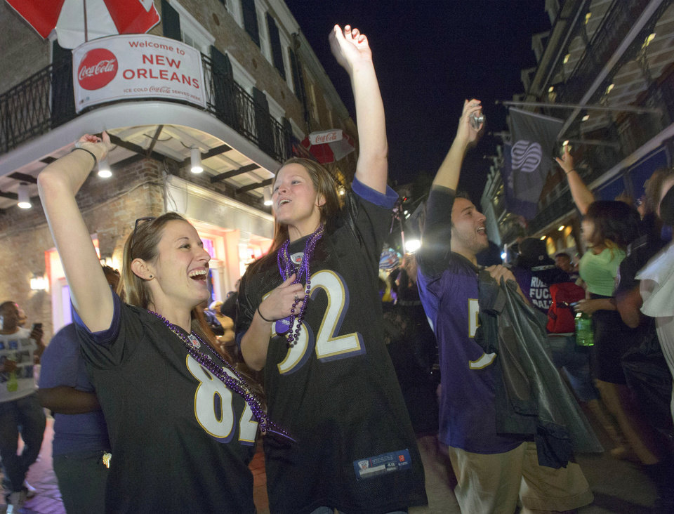 Photo - Baltimore Ravens fans celebrate the team's victory as fans from the Ravens and San Francisco 49ers NFL football teams pack the French Quarter on Bourbon Street for Super Bowl XLVII in New Orleans, Sunday, Feb. 3, 2013. (AP Photo/Matthew Hinton)