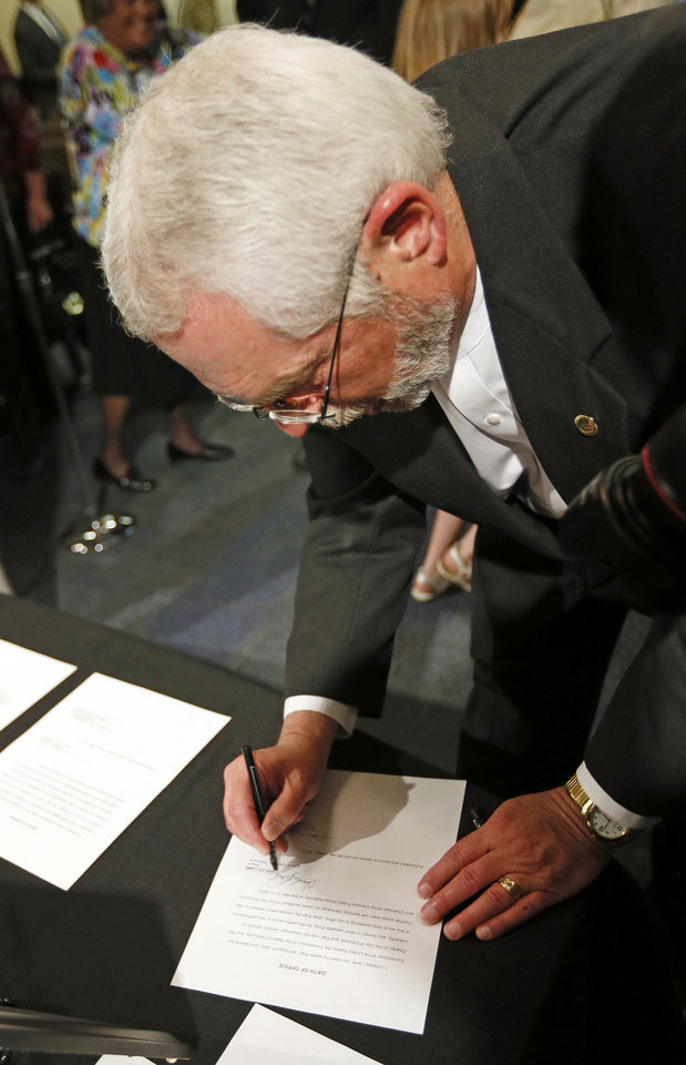 Photo - Edmond Mayor Charles Lamb signs the oath of office during swearing-in ceremonies. PHOTO BY NATE BILLINGS, THE OKLAHOMAN.  NATE BILLINGS - THE OKLAHOMAN