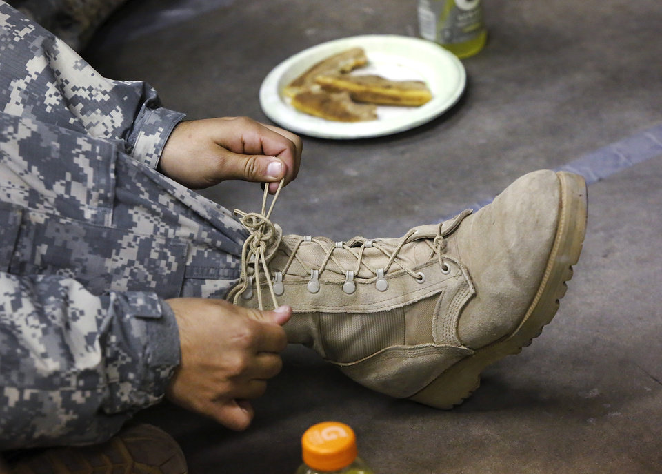 A soldier re-ties the laces on his boots while waiting in the welcome center. Nearly 700 soldiers from Ft. Sill, most of whom had recently completed their basic training, arrived at Will Rogers World Airport on buses in pre-dawn hours Thursday, Dec. 20, 2012, to catch flights to join join their families for the Christmas holidays. The troops were welcomed by Blue Star Mothers and other volunteers at the YMCA Military Welcome Center, where they were offered pizzas, doughnuts, chips, sub sandwiches, desserts, hot coffee and cold beverages. Local merchants donated 250 pizzas, 60 dozen doughnuts and the submarine sandwiches. Photo by Jim Beckel, The Oklahoman