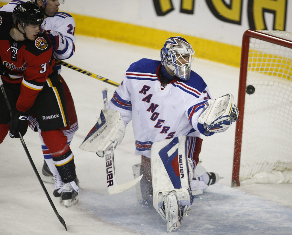 Photo - New York Rangers goalie Henrik Lundqvist, right, from Sweden, looks back as the puck enters the net and Calgary Flames' Paul Byron looks for a rebound during the first period of an NHL hockey game in Calgary, Alberta, Friday, March 28, 2014. (AP Photo/The Canadian Press, Jeff McIntosh)