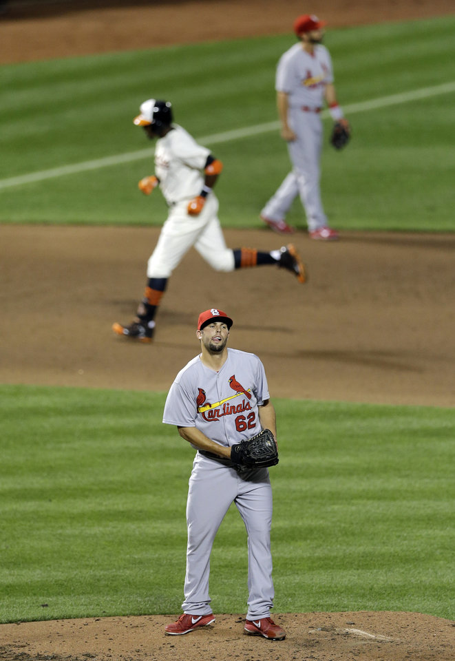 Photo - St. Louis Cardinals relief pitcher Nick Greenwood stands on the mound as Baltimore Orioles' Adam Jones rounds the bases after hitting a solo home run in the fifth inning of an interleague baseball game, Friday, Aug. 8, 2014, in Baltimore. Baltimore won 12-2. (AP Photo/Patrick Semansky)