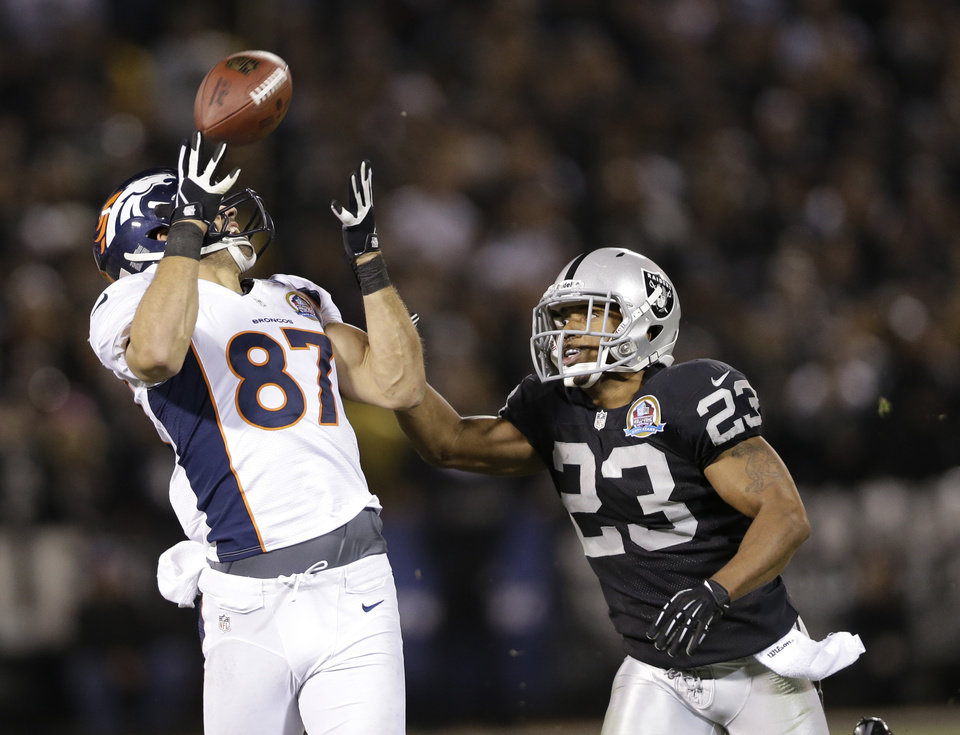 Denver Broncos wide receiver Eric Decker, left, catches a pass at Oakland Raiders defensive back Joselio Hanson, right, looks on during the third quarter of an NFL football game in Oakland, Calif., Thursday, Dec. 6, 2012. (AP Photo/Marcio Jose Sanchez)