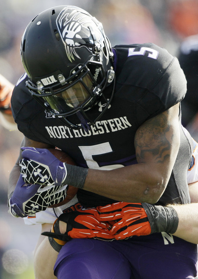 Photo -   Northwestern running back Venric Mark (5) is tackled by Illinois linebacker Mike Svetina (34) during the first half of an NCAA college football game in Evanston, Ill., Saturday, Nov. 24, 2012. Northwestern won 50-14. (AP Photo/Nam Y. Huh)
