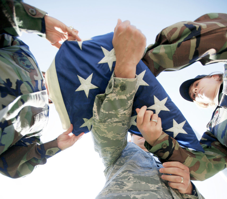 From left to right, Tech. Sgt. Amy Odom, Master Sgt. Jason Noreen and Senior Airman Molly Wittry fold an American flag at Tinker Air Force Base.  OKLAHOMAN ARCHIVE PHOTO BY SARAH PHIPPS