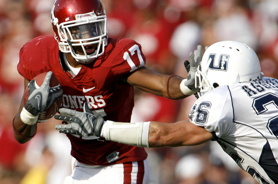 Photo - Mossis Madu of OU tries to get past James Brindley of Utah State in the second half during the University of Oklahoma Sooners (OU) college football game against Utah State University at the Gaylord Family -- Oklahoma Memorial Stadium, on Saturday, Sept. 15, 2007, in Norman, Okla.  By Bryan Terry, The Oklahoman     ORG XMIT: KOD