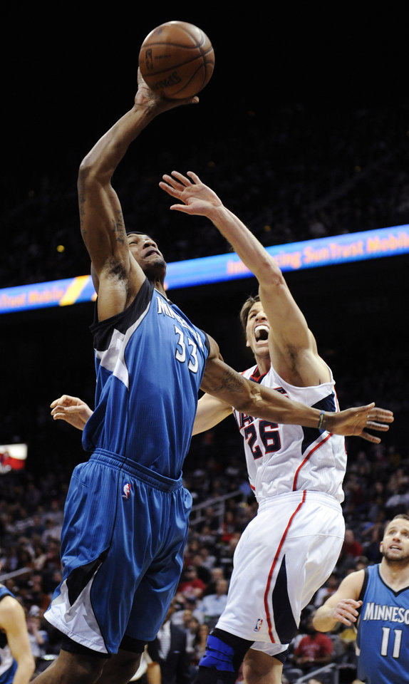 Minnesota Timberwolves forward Dante Cunningham (33) shoots as Atlanta Hawks guard Kyle Korver (26) defends during the second half on an NBA basketball game in Atlanta, Monday, Jan. 21, 2013. Atlanta won 104-96. (AP Photo/John Amis)