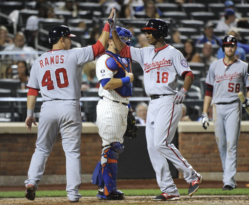 Photo - Washington Nationals' Michael A. Taylor (18) celebrates with Wilson Ramos after Taylor hit a two-run home run during the sixth inning of a baseball game against the New York Mets Tuesday, Aug.12, 2014, at Citi Field in New York. It was Taylor's first career major league home run. (AP Photo/Bill Kostroun)