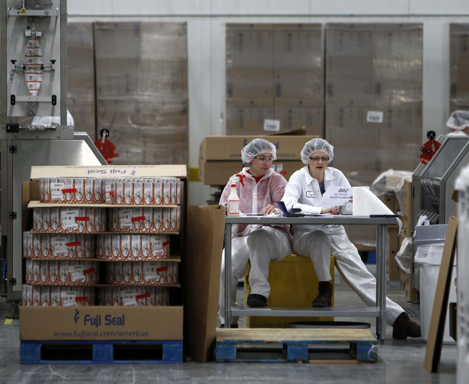 Photo - FILE -- In this Jan. 13, 2012 file photo, two women work in the sleeving plant where labels are put on containers at Chobani Greek Yogurt in South Edmeston, N.Y. Team USA sponsor Chobani, which is based in upstate New York, says it has 5,000 cups of Greek yogurt sitting in a refrigerated warehouse waiting to be flown to the Olympic village. But Russian authorities say the U.S. Department of Agriculture has refused to provide a certificate that is required for dairy products under its customs rules. A U.S. Department of Agriculture spokeswoman says the agency is working with its Russian counterpart to reach a solution to allow the Chobani shipment to go through despite the lack of agreement on general trade requirements for dairy products.(AP Photo/Mike Groll, File)