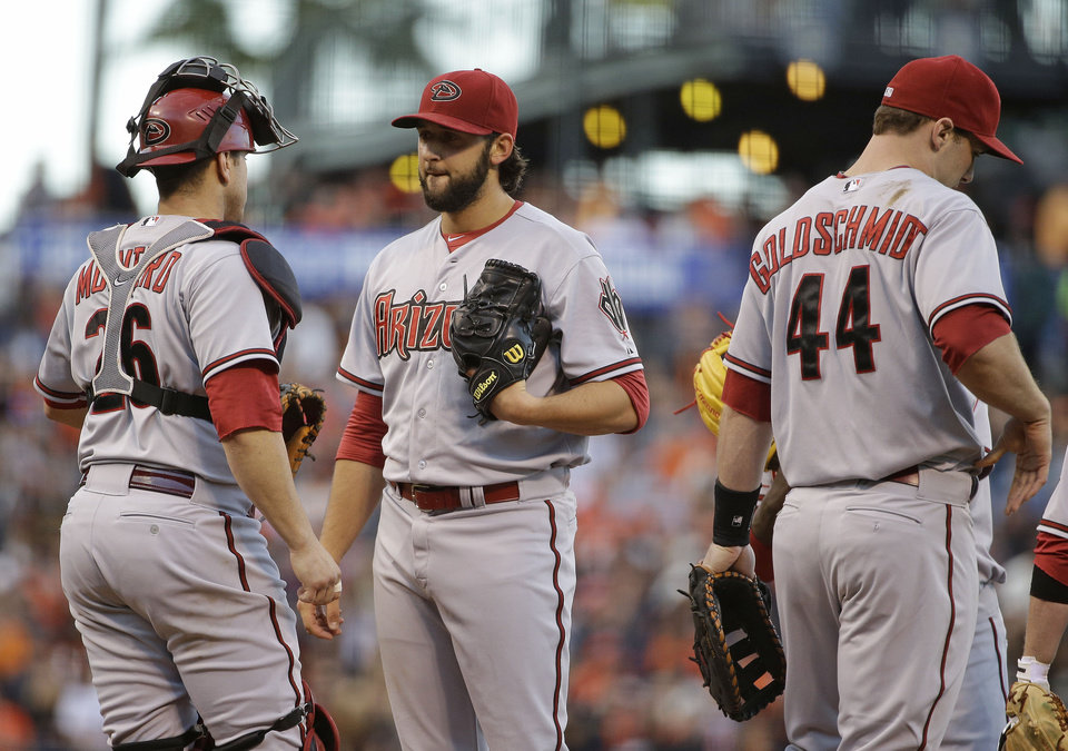 Photo - Arizona Diamondbacks starting pitcher Mike Bolsinger, center, talks with catcher Miguel Montero, left, after the San Francisco Giants scored their third run in the second inning of their baseball game on Friday, July 11, 2014, in San Francisco. First baseman Paul Goldschmidt, right, looks on.  San Francisco won the game 5-0. (AP Photo/Eric Risberg)