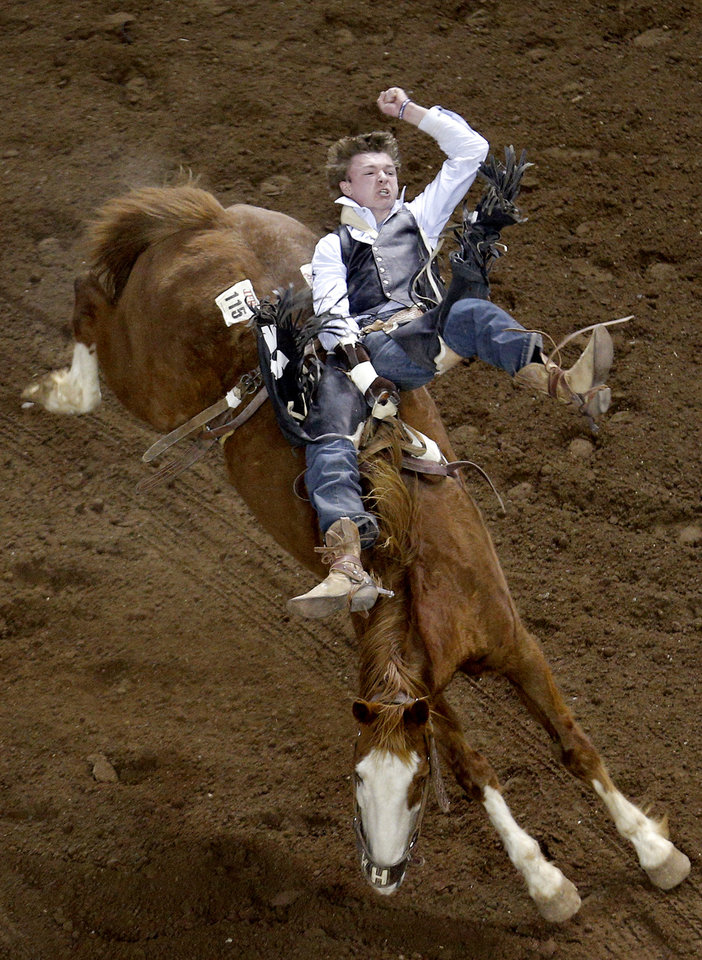 Photo - Mark Justin Kreder of Collinsville, Okla., rides in the bareback born during the International Finals Rodeo at the State Fair Arena in Oklahoma City, Friday, Jan. 17, 2014.  Photo by Sarah Phipps, The Oklahoman