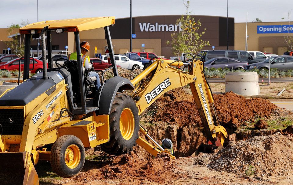 Photo -  Workers bury conduit that will carry electrical connections to a gas station that will be built on the property of Choctaw's first Walmart, scheduled to open in mid-July. Photo by Jim Beckel, The Oklahoman   Jim Beckel -