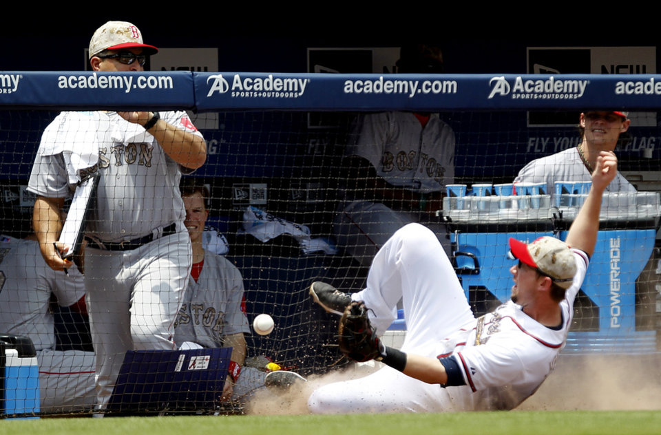 Photo - Atlanta Braves' Chris Johnson (23) nearly misses catching a foul ball as he slides towards the Boston Red Sox dugout during the second inning of a baseball game on Monday, May 26, 2014, in Atlanta, Ga. (AP Photo/Butch Dill)