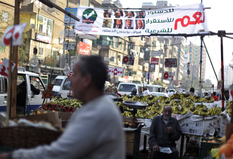 "An Egyptian fruit vendor waits for customers under a banner with Arabic writing that reads, ""Yes to the constitution, stability, and Shariah,"" during a referendum on a disputed constitution drafted by Islamist supporters of President Mohammed Morsi, in Cairo, Egypt, Saturday, Dec. 15, 2012. Egyptians were voting on Saturday on a proposed constitution that has polarized their nation, with Morsi and his Islamist supporters backing the charter, while liberals, moderate Muslims and Christians oppose it. (AP Photo/Khalil Hamra)"