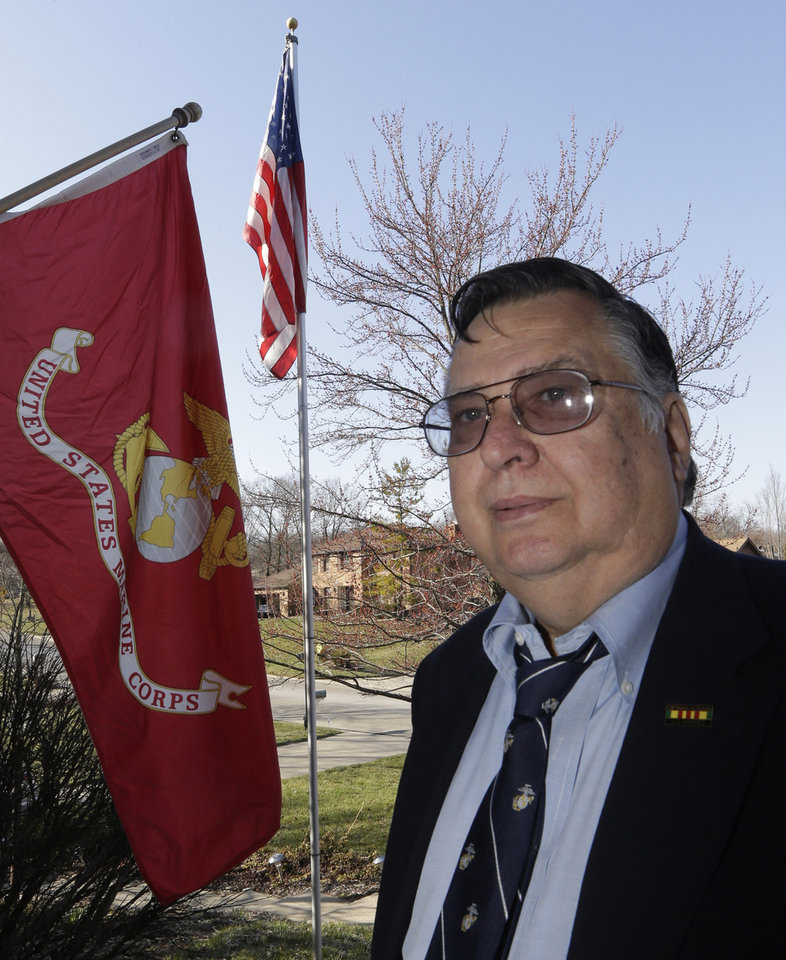 Photo - Marine veteran Harry Prestanski, 65, poses outside his home next to U.S. Marine Corps flag, Thursday, March 28, 2013, in West Chester, Ohio. Prestanski served 16 months as a Marine in the Vietnamese War and remembers having to celebrate his 21st birthday there. (AP Photo/Al Behrman)