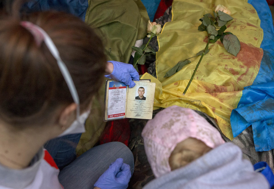 Photo - A paramedic looks at the identification document of a killed anti-government protester, in central Kiev, Ukraine, Thursday, Feb. 20, 2014. A brief truce in Ukraine's embattled capital failed Thursday, spiraling into fierce clashes between police and anti-government protesters. (AP Photo/Darko Bandic)