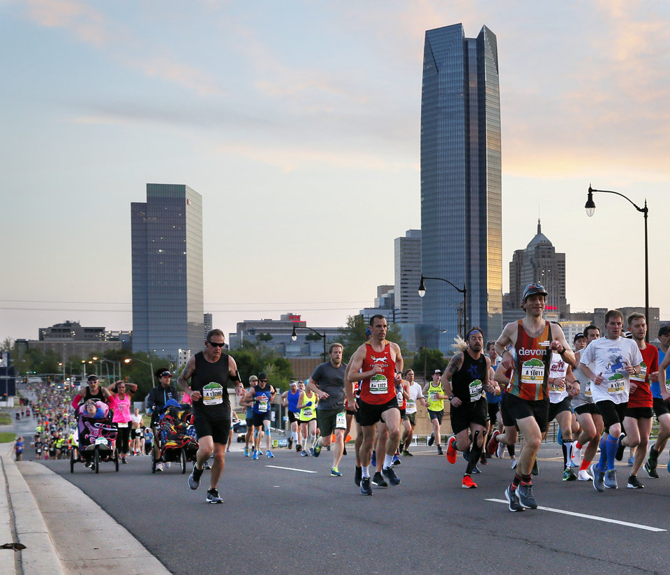 Photo - Runners cross the bridge over Interstate 40 at Walker Ave. going south during the Oklahoma City Memorial Marathon in Oklahoma City, Sunday, April 28, 2019. [Nate Billings/The Oklahoman]