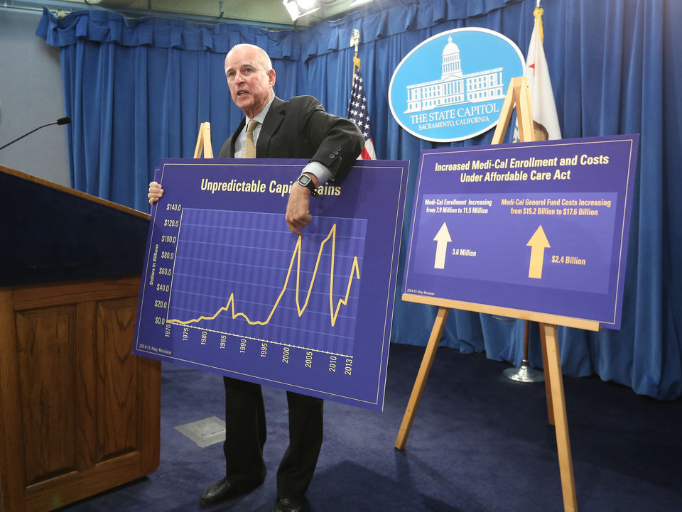 Photo - Gov. Jerry Brown holds a chart showing the unpredictable nature Capitol gains tax revenues have on the state budget as he unveils his revised 2014-15 spending plan at the Capitol in  Sacramento, Calif., Tuesday, May 13, 2014.  The revised budget projects $107.7 billion in spending from the general fund, that's nearly $1 billion more than the budget Brown proposed in January.(AP Photo)