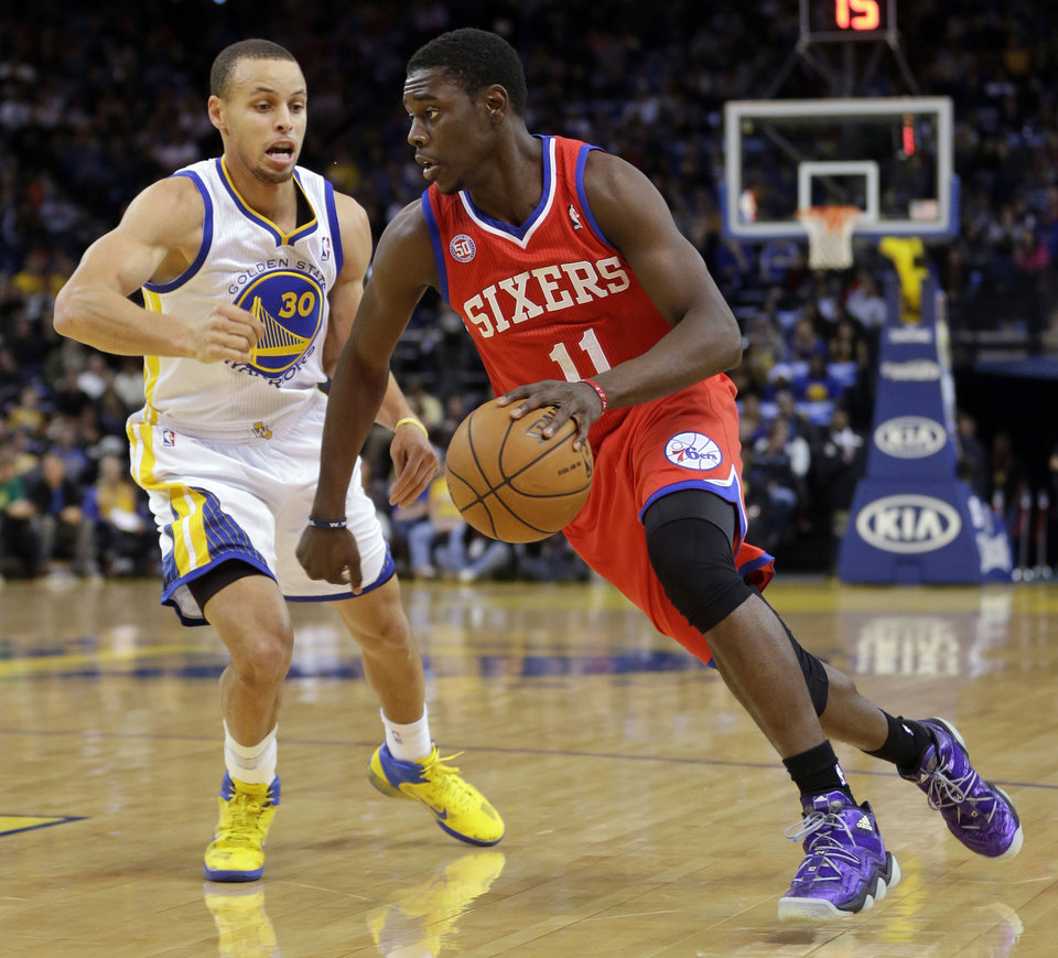 Photo - Philadelphia 76ers' Jrue Holiday (11) dribbles past Golden State Warriors' Stephen Curry (30) during the first half of an NBA basketball game in Oakland, Calif., Friday, Dec. 28, 2012. (AP Photo/Marcio Jose Sanchez)