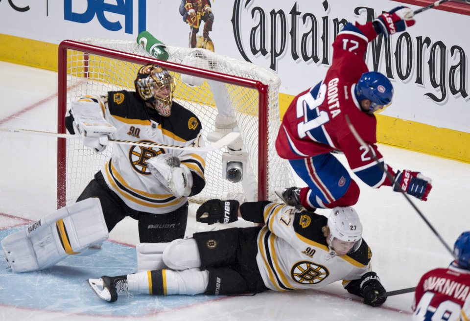 Photo - Montreal Canadiens' Brian Gionta leaps over Boston Bruins' Dougie Hamilton next to goalie Tuukka Rask during second period NHL hockey action Thursday, Dec. 5, 2013, in Montreal. (AP Photo/The Canadian Press, Paul Chiasson)