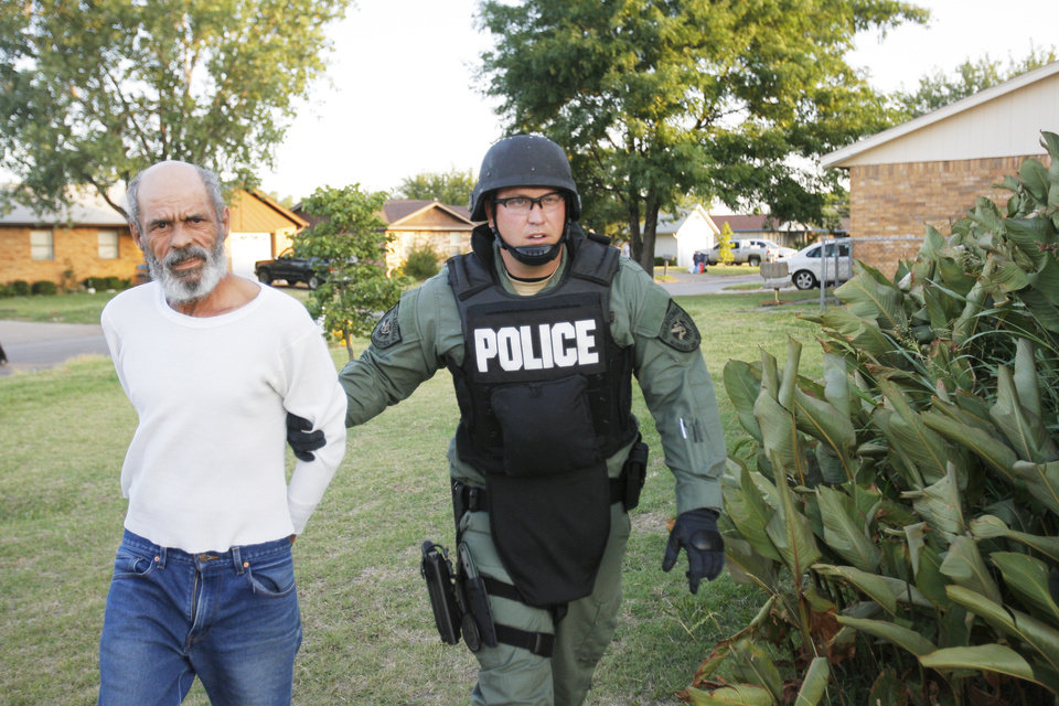 Photo - An Oklahoma Bureau of Narcotics agent takes Lorenzo Franco into custody during a meth raid. Oklahoma Bureau of Narcotics executed a large-scale raid Tuesday morning, July 14, 2009, in Caddo County, launching out of Anadarko,   Photo By David McDaniel, The Oklahoman.