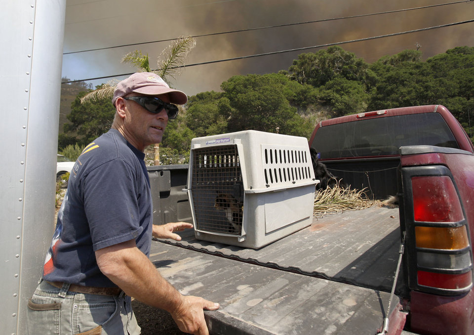 Photo - Kim Rounds loads his cat into his truck as Lompoc residents were order to evacuate from the fast moving Miguelito Fire Tuesday May 13, 2014. Wildfires pushed by gusty winds chewed through canyons parched by California's drought, prompting evacuation orders for 1,200 homes and businesses in Santa Barbara County. (AP Photo/The Santa Maria Times, Daniel Dreifuss)