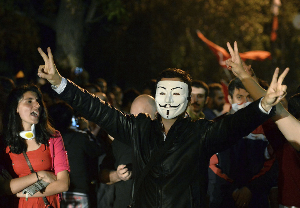 Photo - A Turkish protester wears a Guy Fawkes mask while demonstrating with others on John F. Kennedy street near the U.S. Embassy, in Ankara, Turkey, early Sunday, June 16, 2013.  As Turkish riot police brought an end to an 18-day occupation of an Istanbul park at the center of the strongest challenge to Prime Minister Recep Tayyip Erdogan's 10-year tenure, demonstrations erupted in other cities. In Ankara, at least 3,000 people swarmed into John F. Kennedy street, where opposition party legislators sat down at the front of the crowd facing riot police — not far from Parliament. (AP Photo/Burhan Ozbilici)