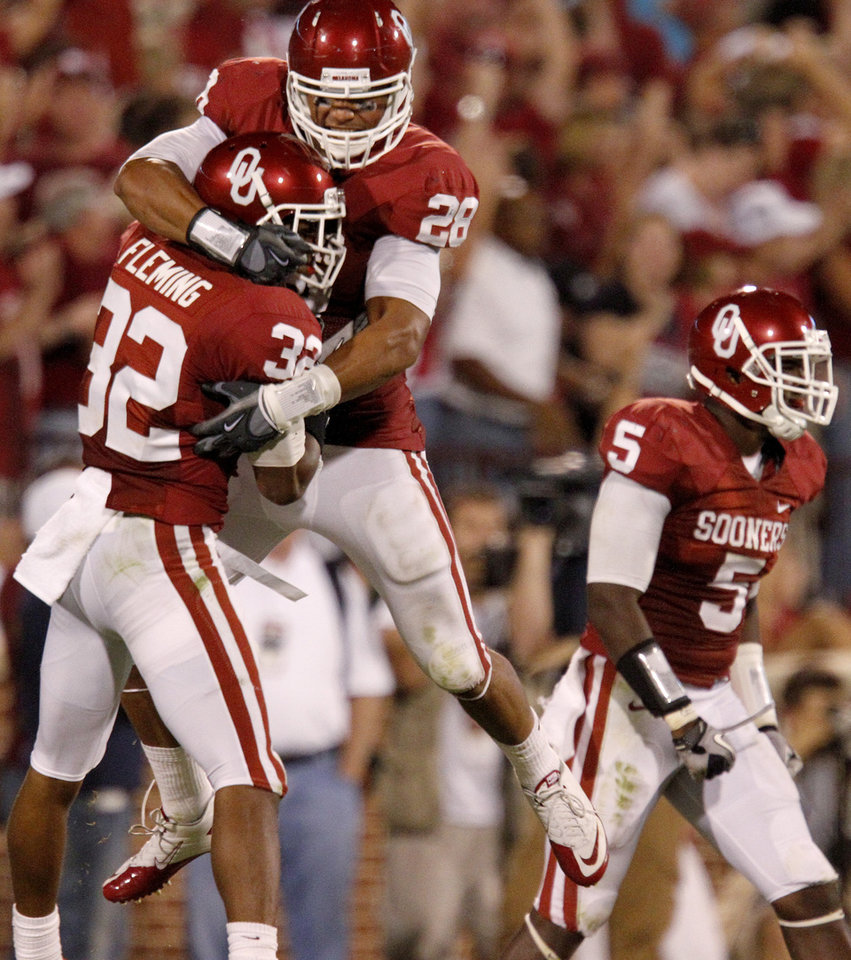 Photo - OU's Jamell Fleming, left, celebrates with Travis Lewis and Joseph Ibiloye after Fleming's interception in the second half of the college football game between the University of Oklahoma Sooners (OU) and Utah State University Aggies (USU) at the Gaylord Family-Oklahoma Memorial Stadium on Saturday, Sept. 4, 2010, in Norman, Okla.   Photo by Bryan Terry, The Oklahoman