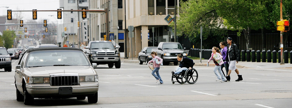 A woman in a wheelchair and children hurry to cross N Hudson Avenue between the County Courthouse and City Hall in this 2009 photo. When walkability consultant Jeff Speck first began addressing pedestrian shortfalls in Oklahoma City, he cited the six-lane wide, one way stretch of Hudson Avenue as an example of street desigh hostile toward pedestrians.  <strong>Jim Beckel - The Oklahoman</strong>
