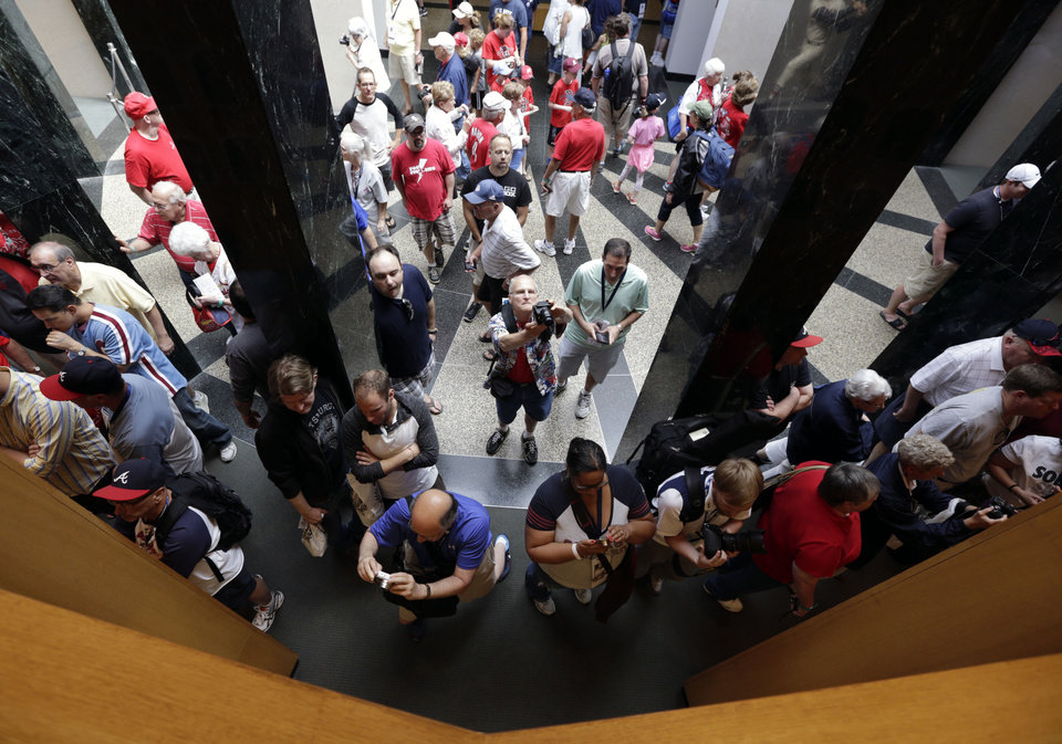 Photo - Fans visit the Plaque Gallery at the Baseball Hall of Fame on Saturday, July 26, 2014, in Cooperstown, N.Y. Former Major League Baseball managers Joe Torre, Bobby Cox and Tony La Russa, with pitchers Greg Maddux and Tom Glavine and slugger Frank Thomas, will be inducted to the hall on Sunday. (AP Photo/Mike Groll)