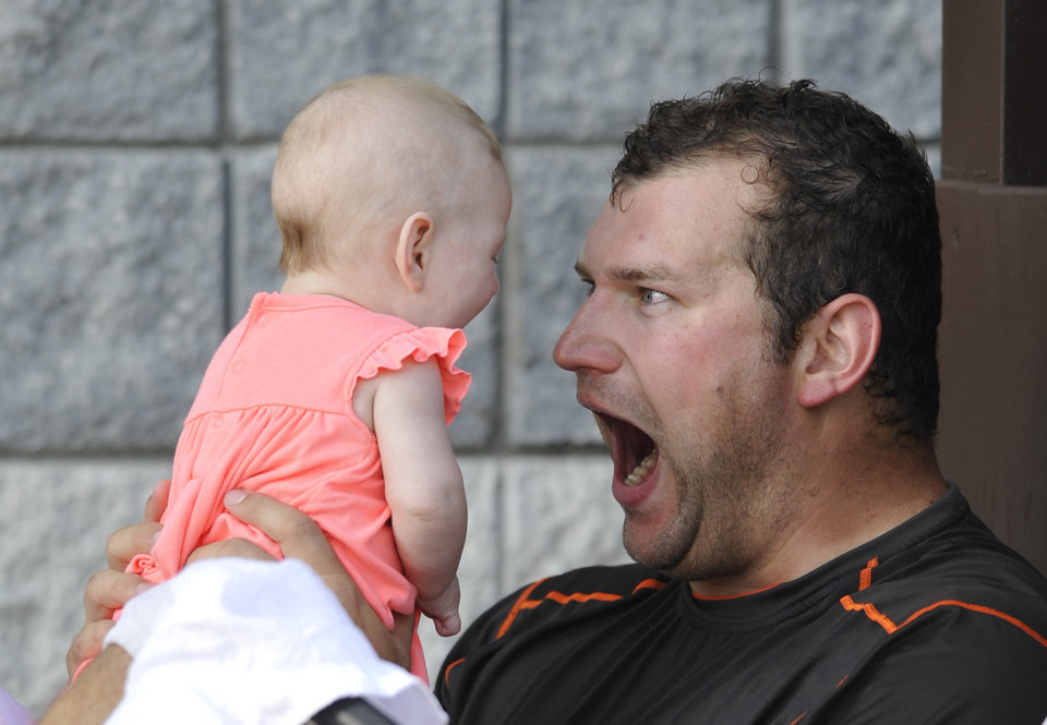 Photo - Cleveland Browns offensive lineman Joe Thomas plays with his daughter Logan Thomas after practice at NFL football training camp at the team's facility in Berea, Ohio, Wednesday, July 31, 2013. (AP Photo/David Richard)