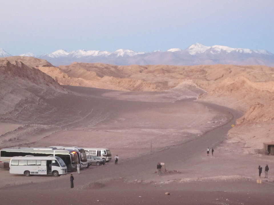 Photo -   This August 2012 photo shows tour buses waiting for visitors to return from watching the sunset over the desolate Valle de la Luna (Moon Valley) in Chile's Atacama Desert. After watching the sun sink in the west, spectators are then treated to a second glowing sky over the Andes. (AP Photo/Karen Schwartz)
