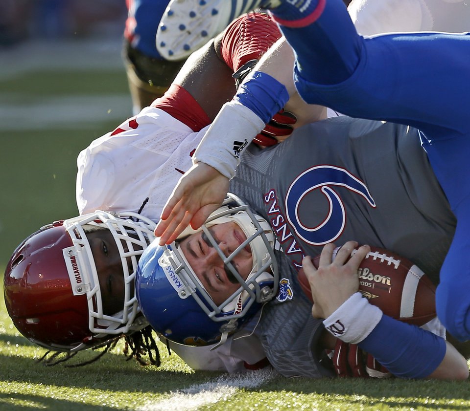 Photo - OU's Charles Tapper (91) brings down KU's Jake Heaps (9) during the college football game between the University of Oklahoma Sooners (OU) and the University of Kansas Jayhawks (KU) at Memorial Stadium in Lawrence, Kan., Saturday, Oct. 19, 2013. Oklahoma won 34-19. Photo by Bryan Terry, The Oklahoman