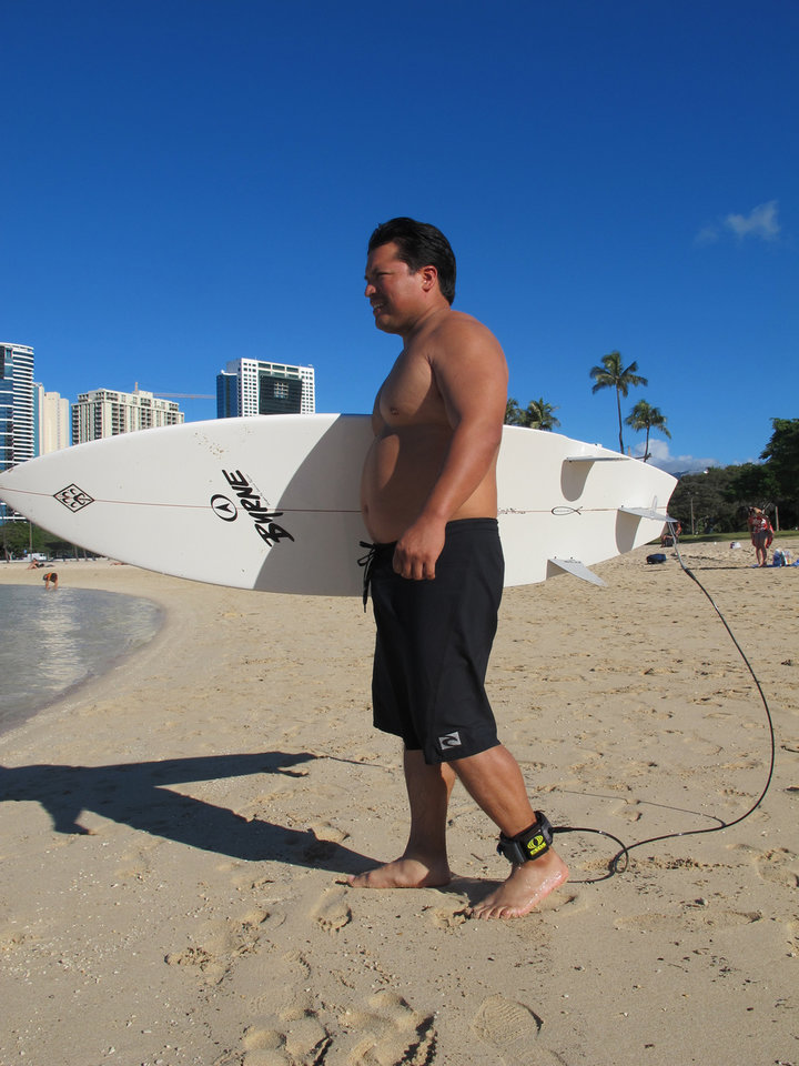 Photo - Rudy Aguilar models a shark deterrent device, the Electronic Shark Defense System, attached to his ankle and surfboard in Honolulu on Dec. 17, 2013. A surge in shark attacks on Maui hasn't stopped people from surfing and swimming in the warm ocean waters that surround this Hawaiian island. But it has spurred sales of devices that claim to keep sharks away by emitting an electric pulse. (AP Photo/Audrey McAvoy)