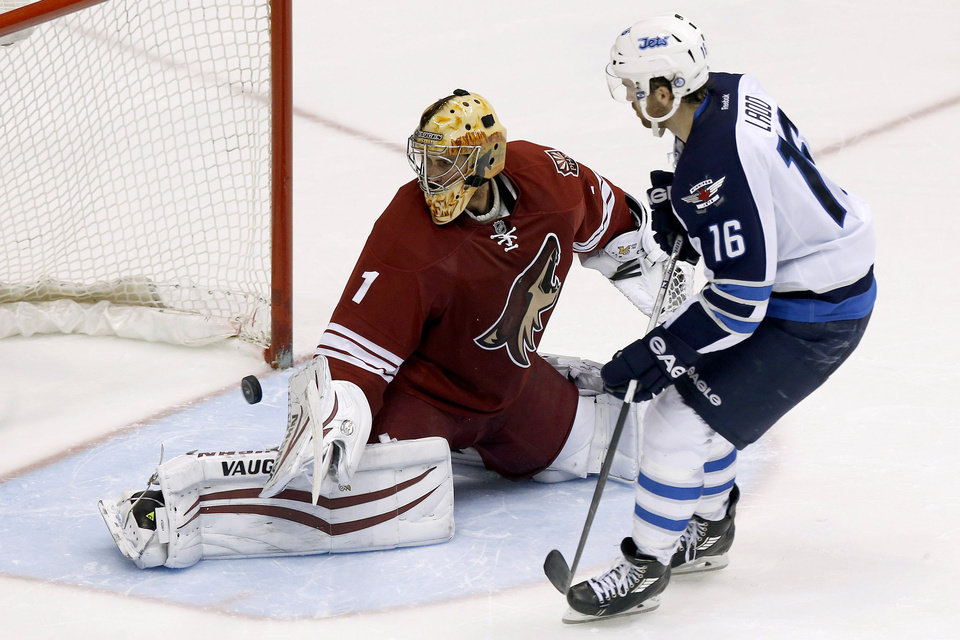 Photo - Winnipeg Jets' Andrew Ladd (16) scores against Phoenix Coyotes' Thomas Greiss (1), of Germany, during a shootout in an NHL hockey game, Tuesday, April 1, 2014, in Glendale, Ariz.  The Jets defeated the Coyotes in a shootout 2-1. (AP Photo/Ross D. Franklin)