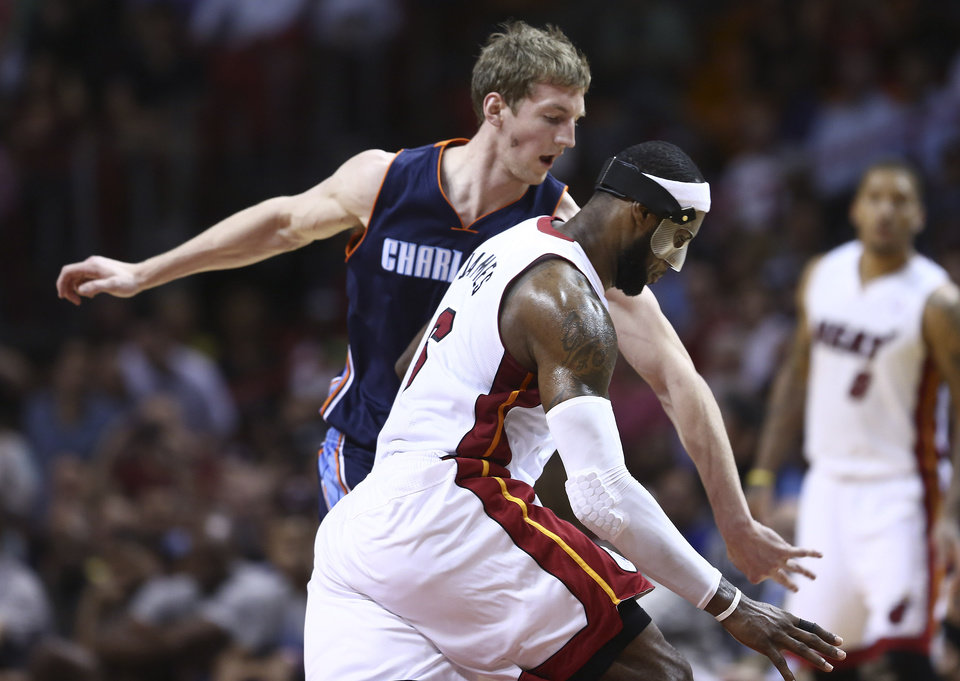 Photo - Charlotte Bobcats' Cody Zeller (40) tries to block Miami Heat's LeBron James (6) during the second half of an NBA basketball game in Miami, Monday, March 3, 2014. James scored a team record of 61 points. The Heat won 124-107. (AP Photo/J Pat Carter)
