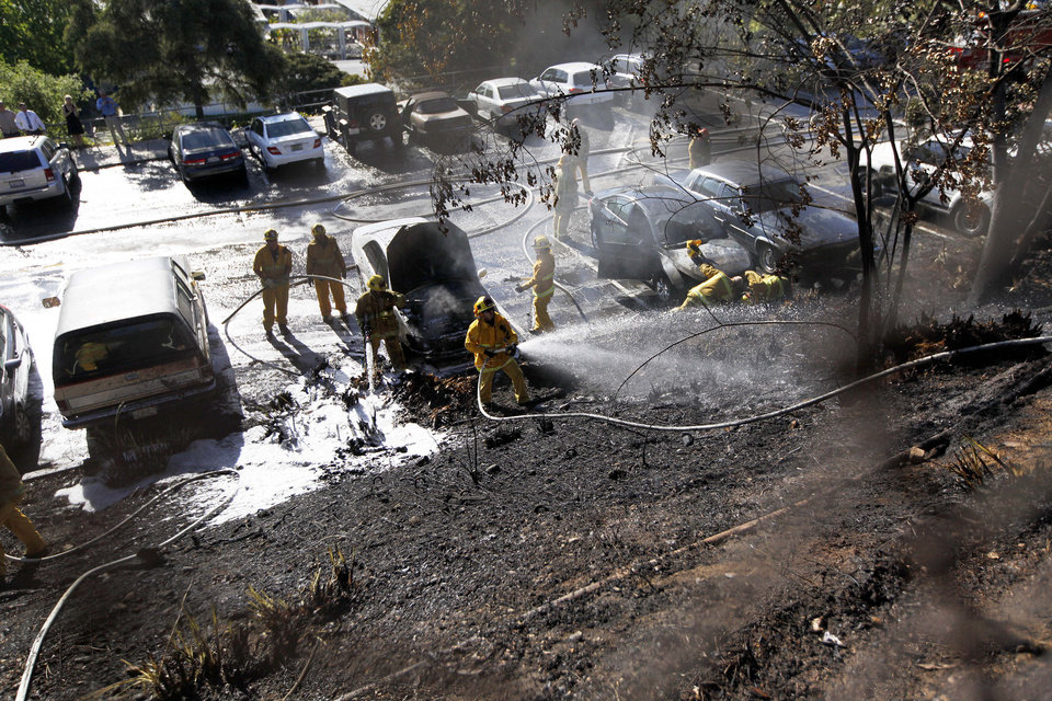 Photo - Los Angeles City firefighters extinguish flames that swept up a hillside behind a parking lot at Palisades Charter High School in the Pacific Palisades area of Los Angeles Thursday, May 15, 2014. It's believed the fire started when a student backed his car into a parking space and its exhaust pipe set off tinder-dry brush. Seven cars were damaged. No injuries were reported. (AP Photo/Reed Saxon)