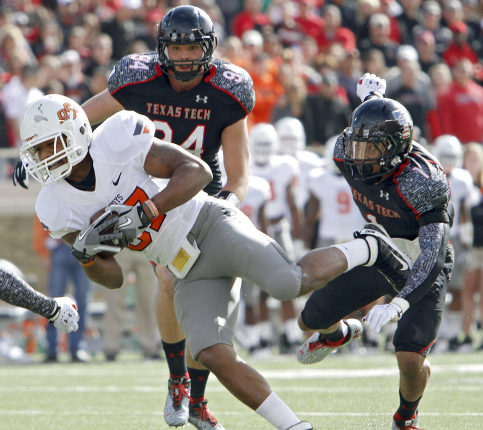Oklahoma State Cowboys wide receiver Tracy Moore (87) makes a catch in front of Texas Tech Red Raiders cornerback Sawyer Vest (34) and Texas Tech Red Raiders safety Terrance Bullitt (1) during the college football game between the Oklahoma State University Cowboys (OSU) and Texas Tech University Red Raiders (TTU) at Jones AT&T Stadium on Saturday, Nov. 12, 2011. in Lubbock, Texas.  Photo by Chris Landsberger, The Oklahoman  ORG XMIT: KOD