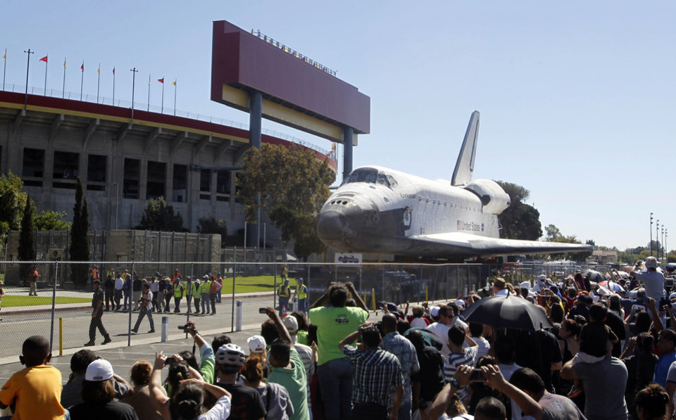 Photo -   The space shuttle Endeavour moves north on Bill Robertson Lane in front of the Coliseum in Los Angeles Sunday, Oct. 14, 2012. In thousands of Earth orbits, the space shuttle Endeavour traveled 123 million miles. But the last few miles of its final journey are proving hard to get through. Endeavour's 12-mile crawl across Los Angeles to the California Science Museum hit repeated delays Saturday, leaving expectant crowds along city streets and at the destination slowly dwindling. Officials estimated the shuttle, originally expected to finish the trip early Saturday evening, would not arrive until later Sunday. (AP Photo/Alex Gallardo)