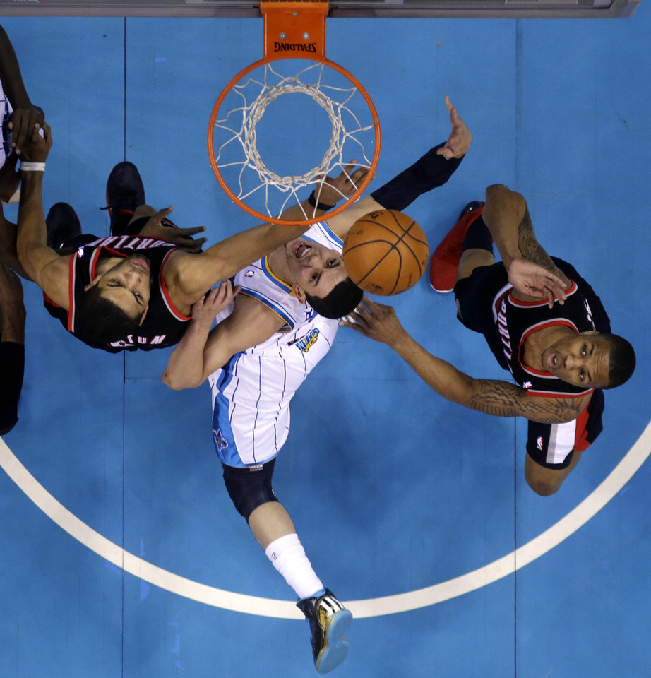 Photo - New Orleans Hornets guard Greivis Vasquez (21) drives to the basket between Portland Trail Blazers' Nicolas Batum, left, and guard Damian Lillard during the first half of an NBA basketball game in New Orleans, Wednesday, Feb. 13, 2013. (AP Photo/Gerald Herbert)