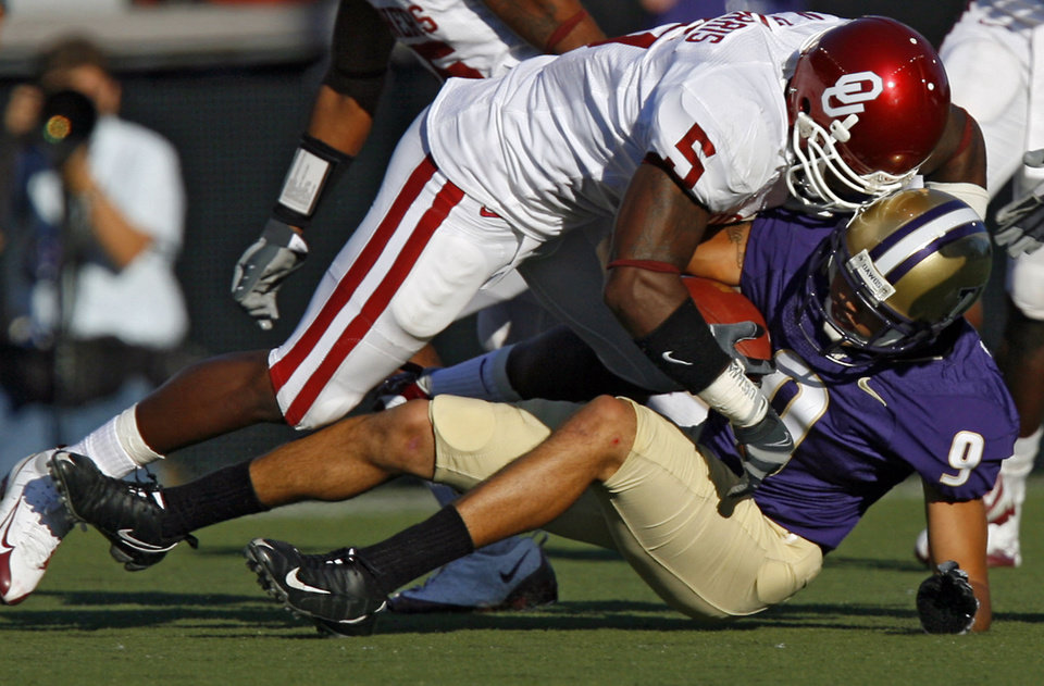 Photo - Oklahoma's Nic Harris (5) stops Washington's Devin Aguilar (9) during the first half of the college football game between the University of Oklahoma Sooners (OU) and the University of Washington Huskies (UW) at Husky Stadium on Saturday, Sep. 13, 2008, in Seattle, Wash. 
