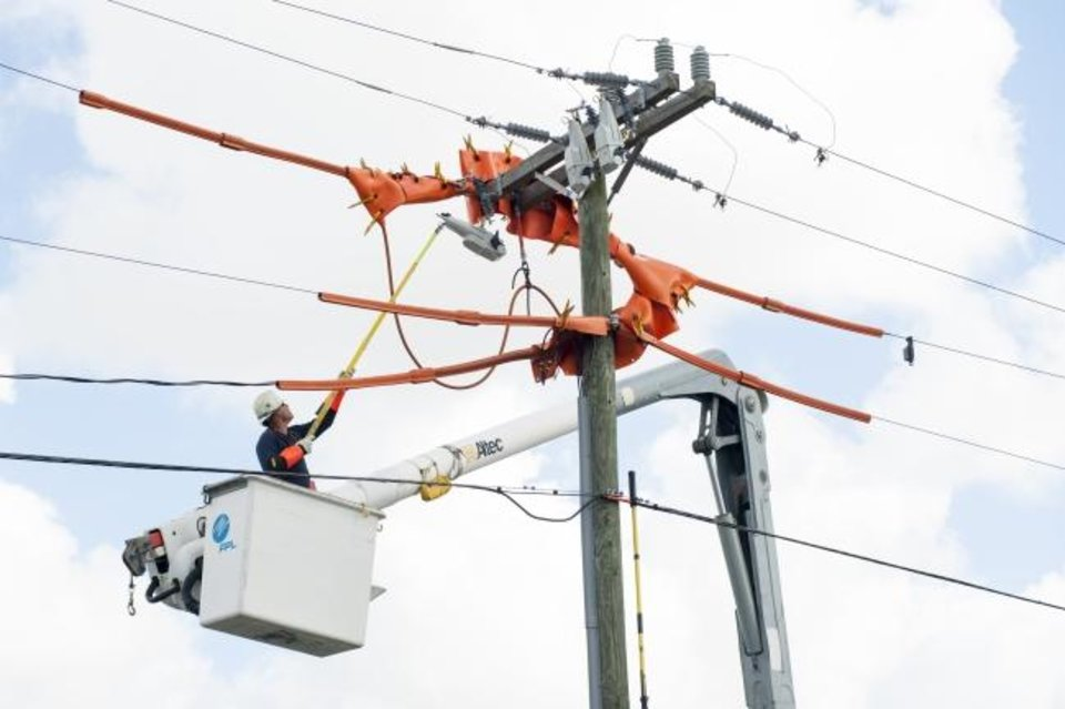 Photo -  A Florida Power and Light lineman installs an Automated Lateral Switch (ALS) on distribution lines in Miami. [PROVIDED BY FLORIDA POWER AND LIGHT]