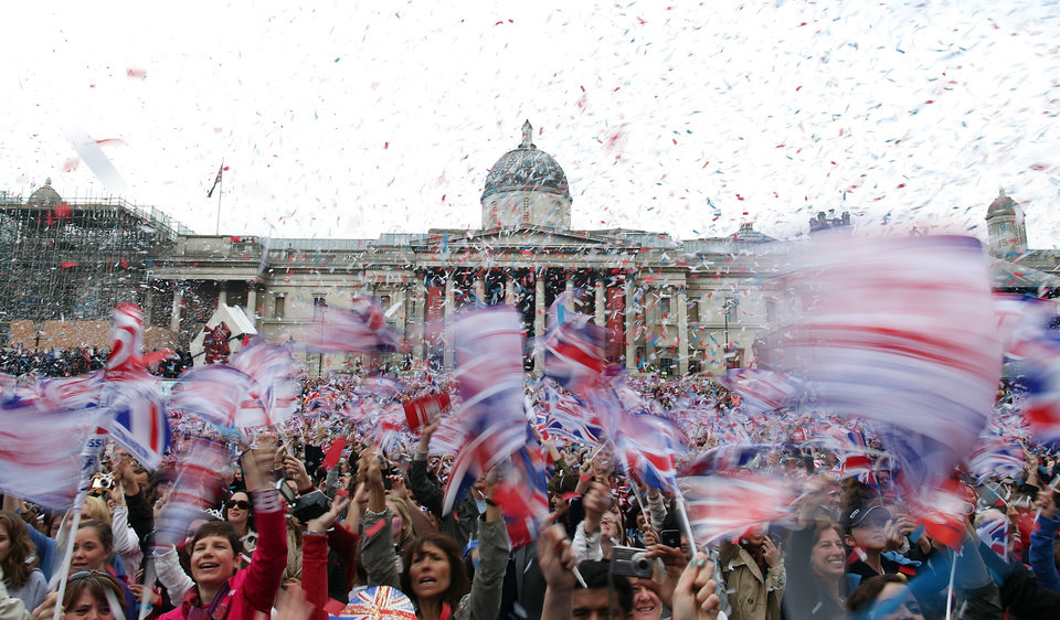Photo - Royal fans wave flags in Trafalgar Square as they watch the wedding of Britain's Prince William and Kate Middleton,in Trafalgar Square in London on Friday, April 29, 2011. (AP Photo/Simon Dawson) ORG XMIT: BSD108