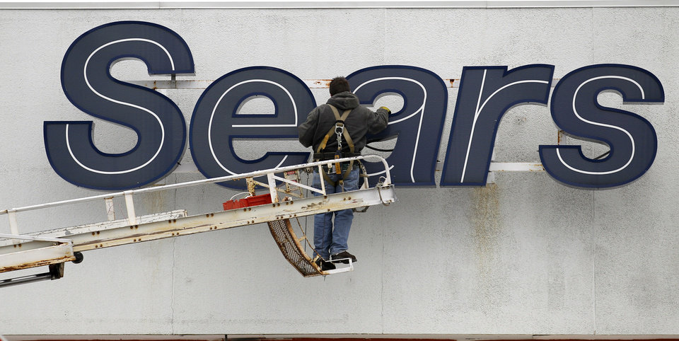 Photo -   In this Feb. 13, 2012 photo, a worker repairs the Sears sign outside the Sears Grand store in Solon, Ohio. Sears Holdings said Thursday, Feb. 23, 2012, it will separate its smaller hometown stores, outlets and some hardware stores in a deal expected to raise $400 million to $500 million as it seeks to regain profitability and market share. (AP Photo/Amy Sancetta)
