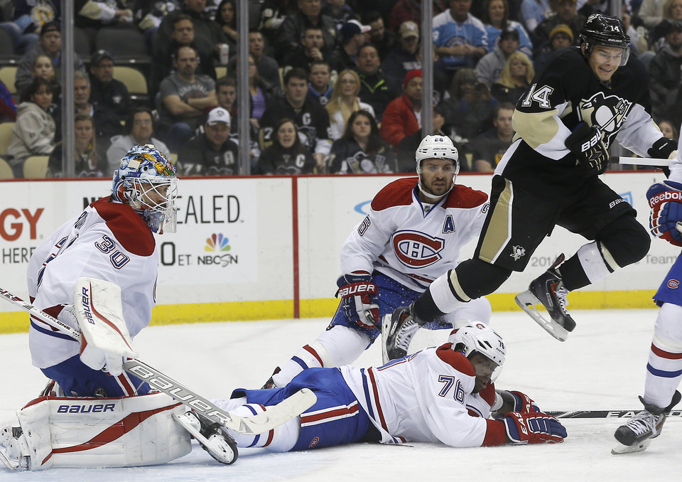 Photo - Pittsburgh Penguins' Chris Kunitz (14) hops over Montreal Canadiens' P.K. Subban (76) as he comes through the goal crease in front of goalie Peter Budaj (30), of Slovakia, during the second period of an NHL hockey game, Thursday, Feb. 27, 2014 in Pittsburgh. (AP Photo/Keith Srakocic)