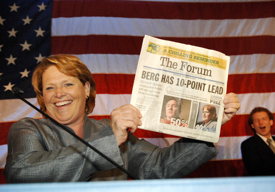 FILE - In this Nov. 7, 2012, file photo, Democratic candidate for North Dakota\'s U.S. Senate seat, Heidi Heitkamp, holds up the Oct. 20, 2012, Fargo Forum in Bismarck, N.D., showing the newspaper had Heitkamp\'s challenger Republican Rick Berg leading Heitkamp in the state by ten points. The grueling political showdown between Heitkamp and Berg in the hotly contested race for U.S. Senate ranked as North Dakota\'s top news story of 2012, according to a vote by Associated Press newspaper and broadcast members. (AP Photo/Will Kincaid, File)