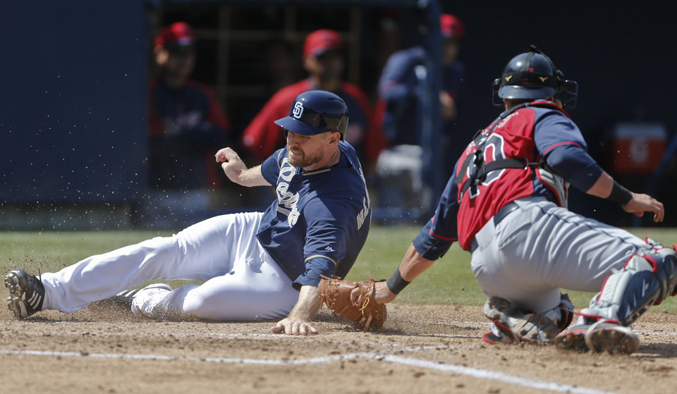 Photo - San Diego Padres' Chase Headley tags homeplate ahead of the tag of Cleveland Indians catcher Yan Gomes while scoring on a triple by Yonder Alonso in the third inning of a spring training exhibition baseball game, Saturday, March 29, 2014, in San Diego. (AP Photo/Lenny Ignelzi)