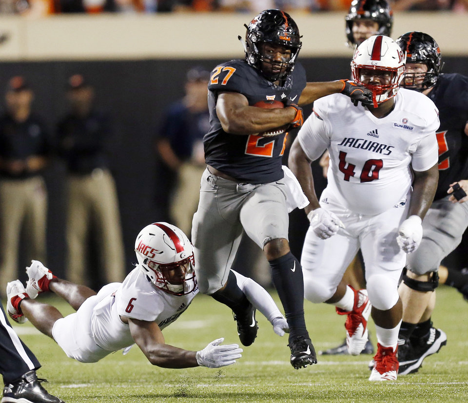 Photo - Oklahoma State's J.D. King (27) runs from South Alabama's Nigel Lawrence (6) and Destin Myers (40) in the second quarter during a college football game between Oklahoma State (OSU) and South Alabama at Boone Pickens Stadium in Stillwater, Okla., Saturday, Sept. 8, 2018. Photo by Nate Billings, The Oklahoman