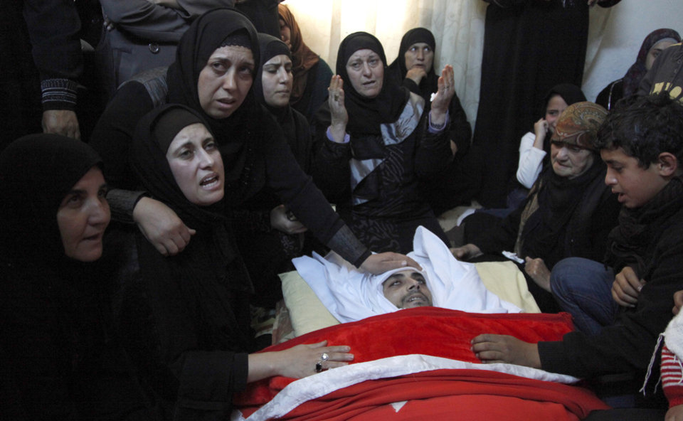 Photo -   The Mother of Qais al Omari, 27, center, and his wife, right to center, and other relatives weep over his body prior to his funeral, Friday Nov. 16, 2012, in Kofr Assad village, Jordan, north of the capital, Amman. Al Omari was shot by Jordanian police, during a demonstration following an announcement of raising fuel prices, including a hike on cooking gas last Tuesday. (AP Photo/Mohammad Hannon)